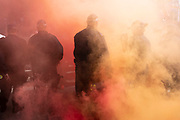 Metropolitan police in riot gear amidst smoke from flares between protesters of the Free Tommy Robinson demonstration, and their opposition organised by anti-fascist groups including Stand up to Racism who are opposed to far right politics on 24th August 2019 in London, United Kingdom. Some 250 Stand Up To Racism and other anti-fascist groups took to the streets today in opposition to supporters of jailed 'Tommy Robinson' real name Stephen Yaxley-Lennon at Oxford Circus, who gathered outside the BBC.
