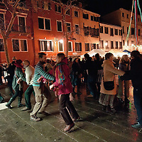"VENICE, ITALY - DECEMBER 18: People dance during a folk music session at ""l'Altro Natale"" Christmas market on December 18, 2010 in Venice, Italy. ""L'Altro Natale"" an alternative Christmas market organised over the busiest shopping week end of the year promotes fair trade and alternative commerce."