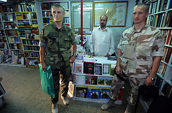 14 August 2005...Danish Army officer pose for a photograph while buying  books at Shahm Book shop in Kabul...Muhammad Rias, in the middle,  says  the Danish buy the  Qur'an most.