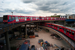 © Licensed to London News Pictures. 23/08/2012, London, UK.  A DLR train crosses over another DLR train as it arrives at West India Quay station in east London, Thursday, Aug. 23, 2012. DLR, Docklands Light Railway, is celebrates its 25th annivesary today. Photo credit : Sang Tan/LNP