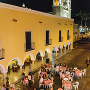 Diners enjoy the warm weather by dinging outside on the closed-off street for the Queen of the Maya 2011 Festival in downtown Valladolid, Mexico. In the background are the two steeples of the Cathedral of San Gervasio.