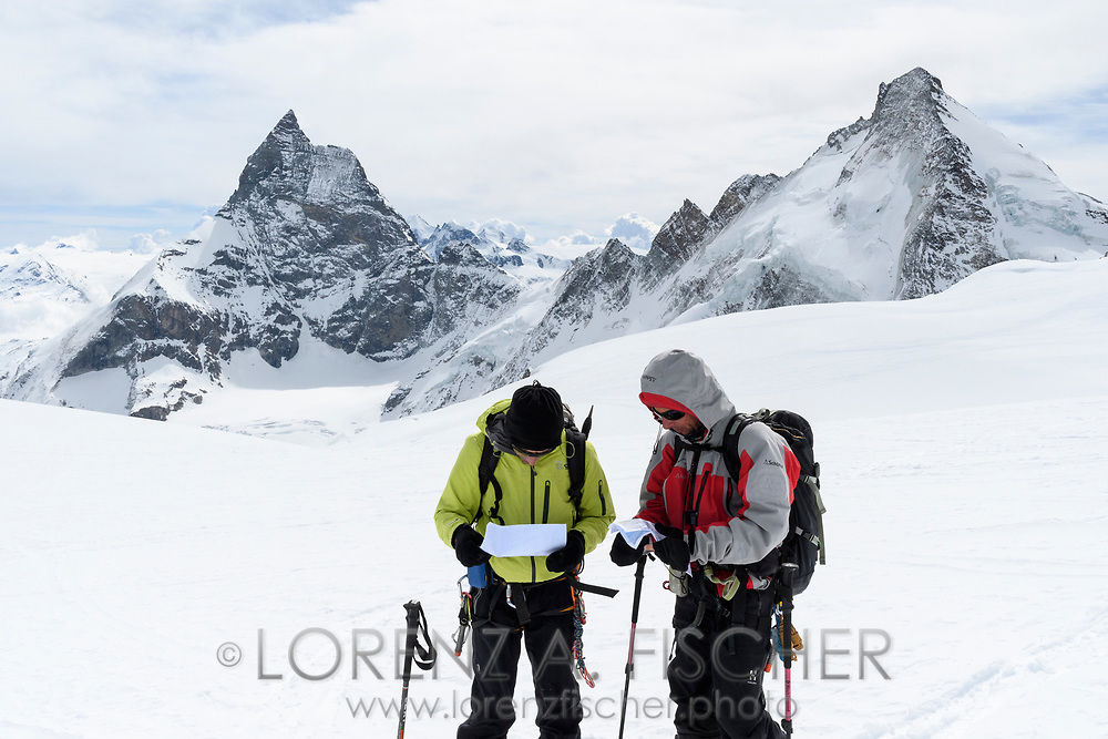 Matterhorn, Dent d'Herens and two alpinists with maps on the Col de la Tete Blanche, Valais, Switzerland