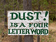 """""""Dust! is a Four Letter Word"""" sign on the dirt road approach to Polebridge, Montana."""