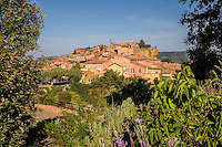 Roussillon, red colored and sitting atop a hill, has been named one of the Plus Beaux Villages de France or the Most Beautiful Villages of France. It's unknown why geological changes should have caused russet pigments here and not elsewhere in Provence.  Roussillon City Office suggests a legend involving a a doomed love affair between a troubadour and a chatelaine in addition to more scientific explanations.  Mining of ochre ceased in Roussillon itself but ochre remains the cornerstone of the town's tourist industry.  The nearby Ochre Trail or Sentier des Ocres is an enjoyable hiking trail through a former ochre quarry.  Place de la Mairie is the main hub of activity as well as Place du Pasquier on Thursday mornings when there's a large market.  Roussillon was famously home to Samuel Beckett who went in hiding in Roussillon after having fled from Paris. Beckett worked on a farm and vineyard while continuing his French Resistance activities.  Beckett referred to Roussillon in his most famous play Waiting for Godot.