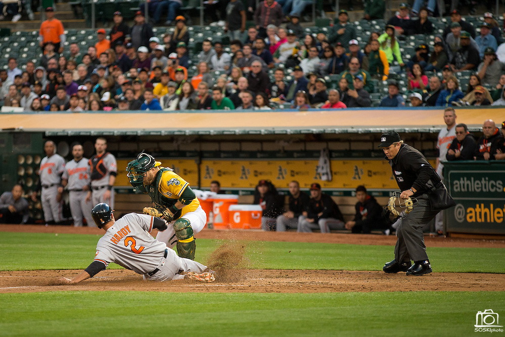 Baltimore Orioles shortstop J.J. Hardy (2) beats a tag at the plate by Oakland Athletics catcher Stephen Vogt (21) during the third inning at Oakland Coliseum in Oakland, Calif. on August 8, 2016. (Stan Olszewski/Special to S.F. Examiner)