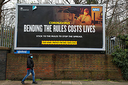 © Licensed to London News Pictures. 01/02/2021. London, UK. A man wearing a protective face covering walks underneath the government's 'Bending the rules costs lives' awareness publicity campaign poster in north London. Covid-19 infection rates are continuing to drop across London. According to a Government scientific adviser, the UK could be easing out of restrictions in March and back to almost normal by summer if vaccines are 70 to 80 per cent effective at blocking transmission. Photo credit: Dinendra Haria/LNP