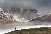 Hiker by mountains in Torres del Paine National Park, Chile