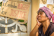 30 JANUARY 2013 - PHNOM PENH, CAMBODIA: A woman who was evicted from her home in a Cambodian land dispute sits next to a hand made sign at a land eviction protest in Phnom Penh, Cambodia. Land disputes in Cambodia are common and many families and sometimes entire communities are evicted as a result of unclear land titles.     PHOTO BY JACK KURTZ