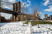 A snowman in Main Street Park surrounded by snow in front of Brooklyn Bridge in Dumbo, Brooklyn, New York City, United States of America.