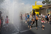 Adults joining in the fun with kids playing in the Appearing Rooms fountains at the Southbank Centre. This Summer water feature / installation is a great draw for families with children, who come to have fun, get wet and lark around in the spray. The South Bank is a significant arts and entertainment district, and home to an endless list of activities for Londoners, visitors and tourists alike.