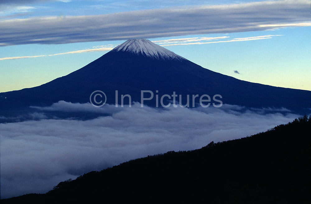 A snow capped Mount Fuji rises above the clouds, Japan<br /> The almost symmetrical mountain is a national sybol for the Japanese and is often climbed by tourists