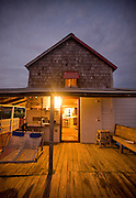 A large porch on a coastal vacation home in Nags Head, North Carolina is lit up at night