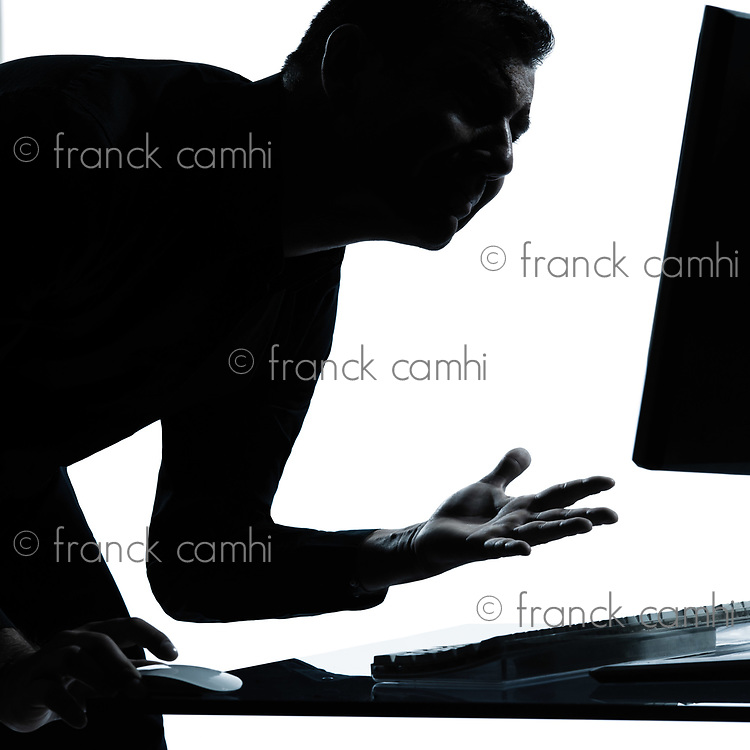 one caucasian business man computing computer angry displeased portrait silhouette in studio isolated on white background