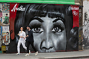 Londoners walk past a recent mural in Shoreditch by artist Jules Muck of Soul Queen Aretha Franklin who died a few days earlier, on 20th August 2018, in London, England.