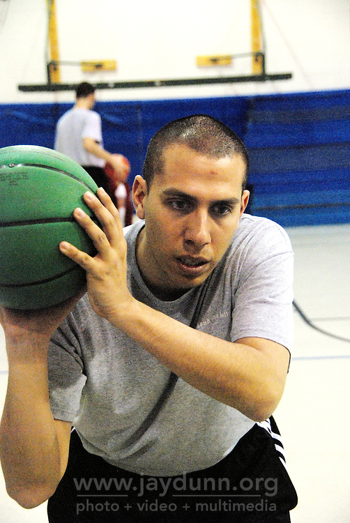"""USA, Chicago, IL, December 16, 2009.  Rob Castaneda demonstrates technique. Founded ten years ago by Rob and Amy Castaneda, """"Beyond the Ball"""" is a non-profit organization dedicated to giving kids and parents a healthy place to play together, whether it be in an after-school program or during an summer series of playground days, like last year's wildly successful """"Project Play."""" The predominantly working-class neighborhoods of Little Village and North Lawndale have no park, and little public space for families that is safe from the gang violence endemic to large US cities. Beyond the Ball's approach is personal, and takes a long-term view - both Rob and Amy are neighborhood residents, and have experienced first-hand the anger of gang members. The group arranges for school facilities to be open late, such as this gym at Josefa Ortiz de Dominguez Elementary, and welcomes student volunteers who also get credit from Chicago Public Schools for doing community service. Many of the teenagers working with """"Beyond the Ball"""" are comfortable as mentors, because they've been in the program before. It is easy to see the pride they take in teaching and taking responsibility for the younger kids, and how such a positive approach to neighborhood building can work. Photo for Hoy by Jay Dunn."""