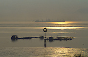 SUNRISE SEA, Malaysia. Early morning mist. Ship. Large vessel on  the horizon. Penang, between Georgetown and Butterworth.