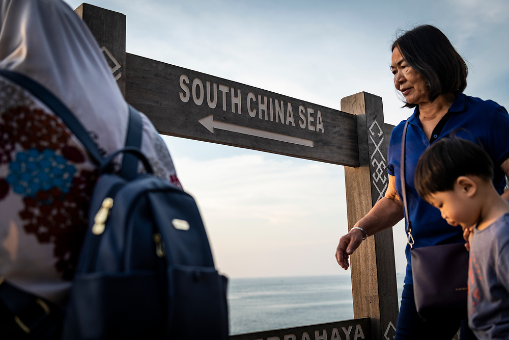 At the northernmost tip of Borneo, located in the Malaysian state of Sabah, visitors walk past a sign pointing toward the direction of the South China Sea. (August 12, 2019)