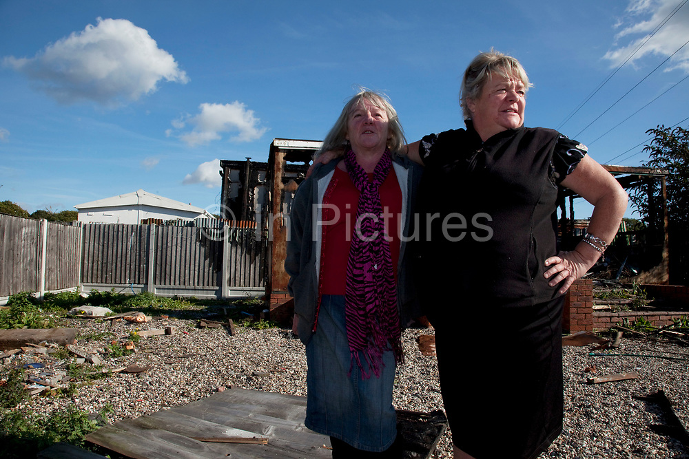 Kathleen McCarthy stands defiantly with her sister Mary beside a burned out building at Dale Farm site prior to eviction. Riot police and bailiffs were present on 20th October 2011, as the site was cleared of the last protesters chained to barricades. Dale Farm is part of a Romany Gypsy and Irish Traveller site in Crays Hill, Essex, UK. <br /> <br /> Senior resident Kathleen McCarthy said she now wished to leave, once obstacles are removed, and the majority of residents are expected to join her. Most plan to relocate to Oak Road, on the neighbouring legal site.<br /> <br /> Dale Farm housed over 1,000 people, the largest Traveller concentration in the UK. The whole of the site is owned by residents and is located within the Green Belt. It is in two parts: in one, residents constructed buildings with planning permission to do so; in the other, residents were refused planning permission due to the green belt policy, and built on the site anyway.
