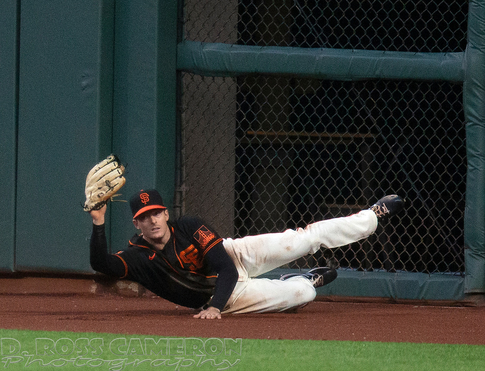Aug 22, 2020; San Francisco, California, USA; San Francisco Giants right fielder Mike Yastrzemski (5) holds up the ball in his glove after making a leaping catch up against the wall of a fly ball off the bat of Arizona Diamondbacks Christian Walker during the sixth inning of a baseball game at Oracle Park. Mandatory Credit: D. Ross Cameron-USA TODAY Sports
