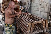 Fisher & lobster pots <br /> Franco Allen<br /> Caye Caulker<br /> Ambergris Caye<br /> Belize<br /> Central America<br /> Fixing out board engine