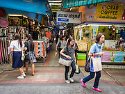 15 JULY 2014 - BANGKOK, THAILAND: Shoppers walk through Siam Square, a shopping and entertainment area in Bangkok. There is a range of shops and services, including tutor schools, restaurants, cafe, designer clothing boutiques, record stores, bookshops, Hard Rock Cafe and banks in the area. Siam Square is owned by Chulalongkorn University and is managed by its Property Management Office, known as the Chula Property.    PHOTO BY JACK KURTZ