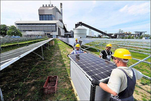 Nederland, The netherlands, Nijmegen, 5-8-2015 Op het terrein van de kolengestookte elektriciteitscentrale van gdf-suez wordt een veld vol zonnepanelen geplaatst en vormt een energiecentrale die stroom opwekt. De oude centrale zal vanaf begin 2016 afgekoppeld worden en gesloopt. De eigenaar gdf-suez wil aan de locatie een groene energiebestemming geven. Zonnecentrale, Field of solar panels create electricity. Foto: Flip Franssen/Hollandse Hoogte