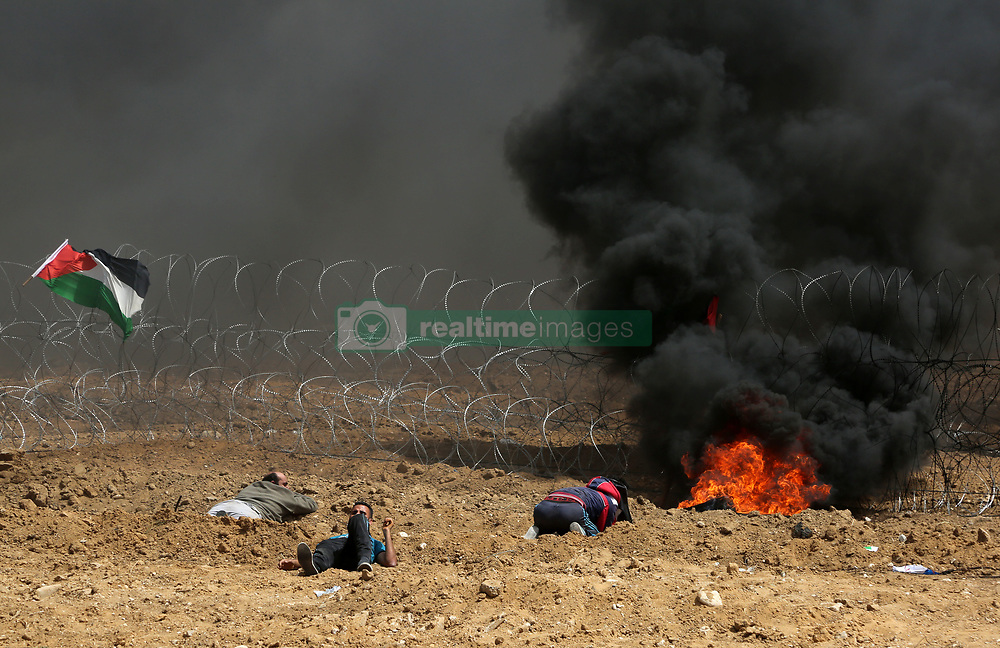 April 13, 2018 - Gaza, Palestinian Territories, Palestine - Palestinians protest near the border fence with Israel, east of Gaza City in the central Gaza Strip on April 13, 2018. Several thousand Gazans gathered for a third consecutive Friday of mass protests along the border with Israel after violence in which Israeli forces have killed 33 Palestinians and wounded hundreds of others. (Credit Image: © Majdi Fathi/NurPhoto via ZUMA Press)