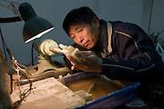 Jade craftsman at work in the Huahui Jade Factory and Showroom, Xian, China