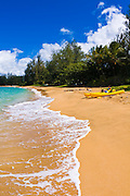 Woman and kayaks on empty beach at Hanalei Bay, Island of Kauai, Hawaii