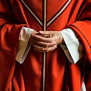A monk wearing a red chasuble is waiting in the sacristy before entering the abbey church in procession for Mass. Solesmes 03-05-16<br /> Un moine portant une chasuble rouge patiente à la sacristie avant d'entrer dans l'église abbatiale en procession pour la messe. Solesmes 03-05-16