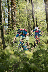 Two mountain bikers speeding on forest path, Bavaria, Germany