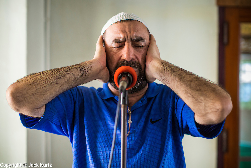 21 FEBRUARY 2013 - BANGKOK, THAILAND:  The muezzin recites the call to prayer in Haroon Mosque in Bangkok.  Haroon Mosque, originally known as Masjid Ton Samrong, is one of the first mosques in Bangkok and was originally built in the middle of the 19th century. It was established by Musa Bafadel, an Indonesian trader from Pantiyanah, south of Borneo in what is now Indonesia. The mosque is now named after Haroon, Musa Bafadel's son who inherited his father's trade empire. The mosque was originally built of wood, but the wood decayed in Bangkok's climate and is now built of bricks and mortar. The wood was salvaged and used in the construction of the mosque.      PHOTO BY JACK KURTZ