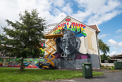 """© Licensed to London News Pictures; 06/08/2021; Bristol, UK. Street artist INKIE uses a mobile platform to work on a giant mural of DJ Derek on the side of a house by Junction 2 of the M32 motorway and passed by 150,000 vehicles a month. Two of the world's most famous street artists are among the team working on the tribute together, Bristol-based Harriet Wood, aka Hazard One has painted the image of DJ Derek, and Inkie is putting the finishing touches to the words and framing around the giant portrait. The project to create a lasting mural to DJ Derek began last year after a previous mural was tagged, and then painted over, to the dismay of family and friends. Artists, music fans and Derek's family came together with a fundraising campaign, that was then boosted by Arts Council backing. DJ Derek was born Derek Serpell-Morris (18 December 1941 – July 2015) and was an English DJ based in Bristol. In a DJ career that spanned over 40 years, he was known for playing a blend of 60s rocksteady, reggae, ska, dancehall and soul. He was reported missing in July 2015 and his remains were found near Cribbs Causeway on 10 March 2016 but police said they were not treating his death as suspicious. A former accountant at Cadburys, Derek began his DJ career in his mid-30s. He said he finished most sets with the Bob Marley hit """"One Love"""", saying it's a perfect signing-off record for a reggae set—let's get together and feel all right. He MCed in Jamaican Patois while DJing. Photo credit: Simon Chapman/LNP."""