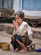 """11 MARCH 2013 - LUANG PRABANG, LAOS:  A woman prays after the tak bat in Luang Prabang. The """"Tak Bat"""" is a daily ritual in most of Laos (and other Theravada Buddhist countries like Thailand and Cambodia). Monks leave their temples at dawn and walk silently through the streets and people put rice and other foodstuffs into their alms bowls. Luang Prabang, in northern Laos, is particularly well known for the morning """"tak bat"""" because of the large number temples and monks in the city. Most mornings hundreds of monks go out to collect alms from people.   PHOTO BY JACK KURTZ"""