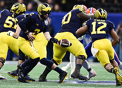 Michigan Wolverines quarterback Shea Patterson (2) Michigan Wolverines defensive lineman Carlo Kemp (2) prepares to hand the ball off too Michigan Wolverines running back Chris Evans (12) during the Chick-fil-A Bowl Game at  the Mercedes-Benz Stadium, Saturday, December 29, 2018, in Atlanta. ( Kyle Hess via Abell Images for Chick-fil-A Kickoff)