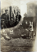 fading image of various generations family portrait  in front of a barn rural France