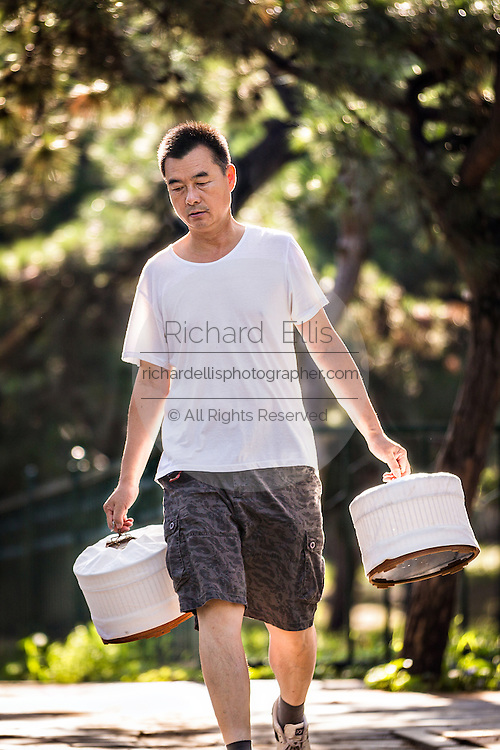 Chinese man walks with his pet singing birds early morning at the Temple of Heaven Park during summer in Beijing, China