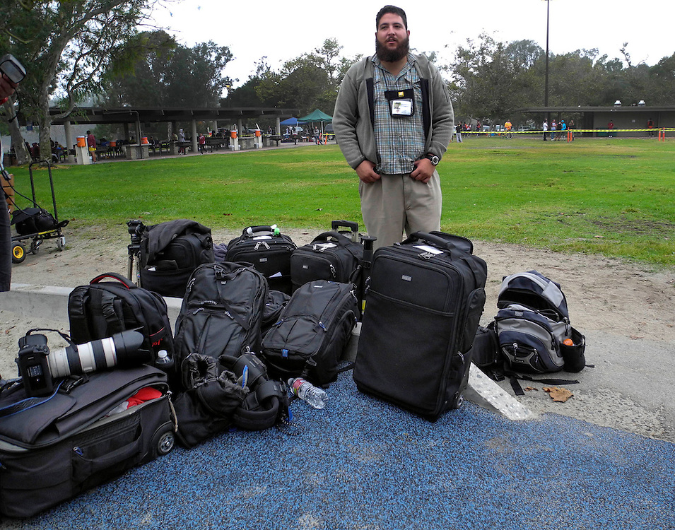 2/29/12  --- SPORTS SHOOTER ACADEMY --- Rafael Delgado stands guard over gear and Think Tank Photo rollers and bags as participants look for shooting positions before a cross country race during Sports Shooter Academy IX. Photo by Robert Hanashiro, Sports Shooter Behind the Scenes with the cast and crew of Sports Shooter Academy.
