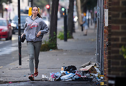 © Licensed to London News Pictures. 27/08/2019. London, UK. A woman walks to work past rubbish and debris on a street in Notting Hill, west London, in the aftermath of the 2019 Notting Hill carnival. The two day event is the second largest street festival in the world after the Rio Carnival in Brazil, attracting over 1 million people to the streets of West London. Photo credit: Ben Cawthra/LNP