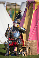McG0064278<br /> A performer in heavy armour cools down with a drink at Portchester Castle in Hampshire where events have been taking place to mark the 600th anniversary of the battle of Agincourt. <br /> In 1415 soldiers left from the castle, now managed by English Heritage, for northern France where they went on to face the French in a muddy farmer's field.<br /> Picture date: Saturday August 8, 2015.<br /> Photograph by Christopher Ison ©<br /> 07544044177<br /> chris@christopherison.com<br /> www.christopherison.com