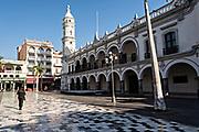 Pedestrians walk along the Plaza de las Armas and the Portales de Veracruz in the historic center of the city of Veracruz, Mexico. The area is the main public square in Veracruz.