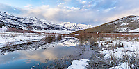 Panoramic view of Mount Timpanogos on an early Winter morning as the sun illuminates the peaks and clouds over a lake in Utah's Wasatch Mountains.