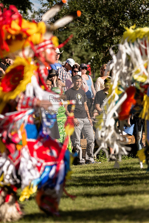 Audience members watch Native Americans dancers from the Arapahoe people dressed in traditional costumes perform a fancy dance at the Indian Village during Cheyenne Frontier Days July 25, 2015 in Cheyenne, Wyoming. Frontier Days celebrates the cowboy traditions of the west with a rodeo, parade and fair.