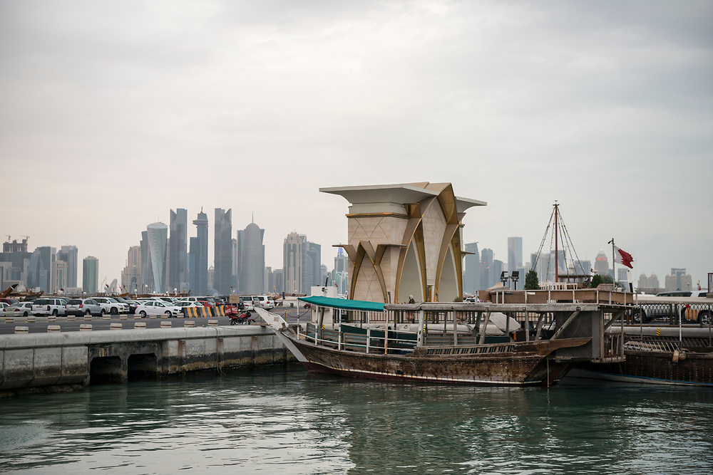 A dhow is tied to a pier in Doha Bay. Across the bay is the modern skyline of Doha, Qatar