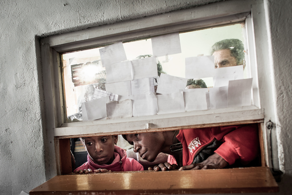 Patients are seen through a small window queuing to register at the public health clinic in Wamena.<br /> <br /> Wamena currently has 1,894-recorded HIV/AIDS cases, and the number continues to rise.  The main public health clinic in Wamena is swamped with over 200 patients a day seeking various forms of health treatment.  Those who want to get tested for HIV must line up in the morning and register with everyone else.  The cramped HIV testing and counseling room is packed with several clients at a time, leaving no room for privacy and confidentiality.  Counselors are unable to spend much time educating patients and addressing their questions.  The lab responsible for processing the HIV test must also conduct lengthy tests for various illnesses including malaria and tuberculosis.  The overwhelming burden on both the staff and the facility reduces the quality of care.  Despite an increasing desire from the public to get tested for HIV, the clinic limits HIV testing to only 10 patients per day.  The director of the clinic believes that the cap is necessary to maintain quality control and ensure accurate test results.  Nevertheless, sometimes as many as 25 patients visit the clinic to get tested for HIV.  When they are turned away, many patients are discouraged to return.