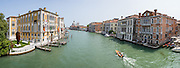 """See Basilica di Santa Maria della Salute from Ponte dell'Accademia bridge on the Grand Canal in Venice, Italy. The bridge links the sestiere of San Marco and Dorsoduro and is named for the Accademia di Belle Arti di Venezia. The original 1854 steel bridge was replaced by a wooden one in 1933 and 1985. Lovers like to attach padlocks (""""love locks"""") to the metal hand rails of the bridge (but are discouraged from doing so by Venice authorities). The yellow and white building at left is Istituto Veneto di Scienze Lettere ed Arti / Palazzo Cavalli Franchetti. Venice (Venezia) is the capital of Italy's Veneto region, named for the ancient Veneti people from the 900s BC. The romantic """"City of Canals"""" stretches across 100+ small islands in the marshy Venetian Lagoon along the Adriatic Sea in northeast Italy, between the mouths of the Po and Piave Rivers. The Republic of Venice was a major maritime power during the Middle Ages and Renaissance, a staging area for the Crusades, and a major center of art and commerce (silk, grain and spice trade) from the 1200s to 1600s. The wealthy legacy of Venice stands today in a rich architecture combining Gothic, Byzantine, and Arab styles. This panorama was stitched from 10 overlapping photos."""