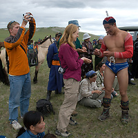 Rural herders and an archaeology team mingle after wrestling matches at a naadam festival on a remote pass near Muren, Mongolia. The winner on right, was one of the archaeologists, much to the locals' dismay.