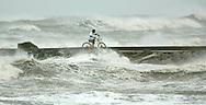 Benny Salas rides his bike on a pier in Galveston, Texas as Hurricane Rita approached September 23, 2005. ..