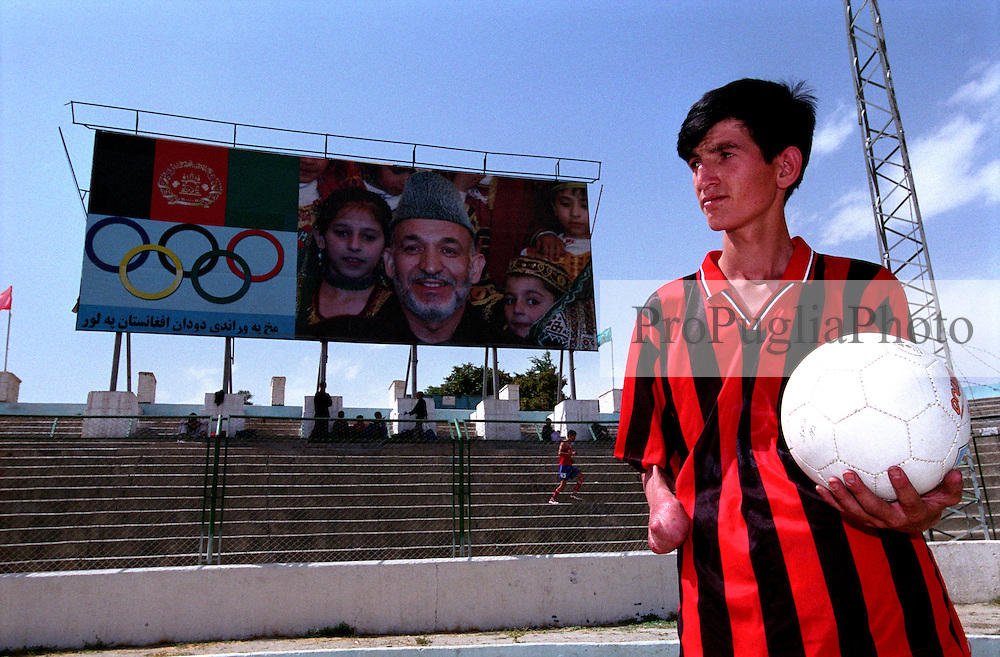 SPECIAL OLYMPICS AFGHANISTAN.KABUL 24 August 2005.Ghazi Stadium..A disable athlete, wearing the Milan football-club's  Tshirt, stands next to the Afghan Olympics bill-board..On 23-25 August 2005, Special Olympics Afghanistan held its first national Games at Olympic Stadium in Kabul. More than 300 athletes, including 80 female athletes, experienced a taste of happiness and achievement for the first time in their lives. They competed in athletics, bocce and football (soccer). Because of cultural restrictions, males and females competed at separate venues.