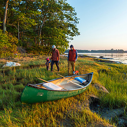 A couple and their young daughter (and dog) walk the shoreline after a night of camping on Lanes Island in Casco Bay. Yarmouth, Maine.